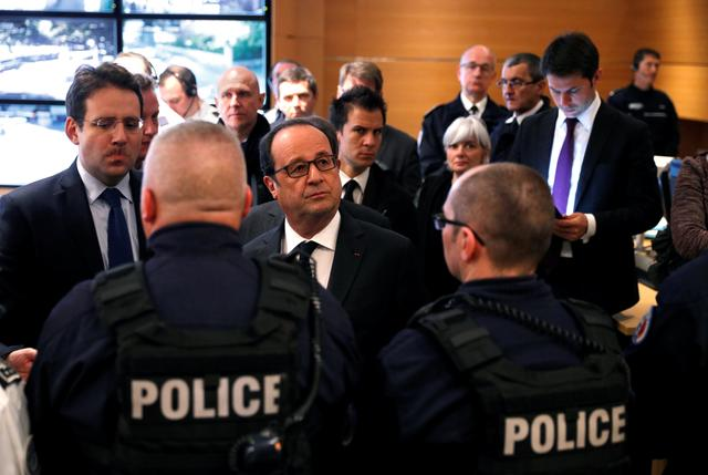French President Francois Hollande (C) and Interior Minister Matthias Fekl (L) speak with policemen at Paris police headquarters the day after a policeman was killed and two others were wounded in a shooting incident on the Champs Elysees Avenue in Paris, April 21, 2017. REUTERS/Philippe Wojazer