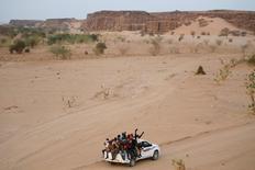 مهاجرون على شاحنة يقطعون الصحراء في طريقهم من أجاديز بالنيجر إلى ليبيا يوم 9 مايو أيار 2016 - رويترز.