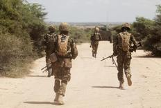 Kenya Defence Forces (KDF) soldiers, who are part of the African Mission in Somalia (AMISOM), secure an area during a foot patrol on the outskirts of the controlled area of the old airport in the coastal town of Kismayu in southern Somalia November 12, 2013. REUTERS/Siegfried Modola