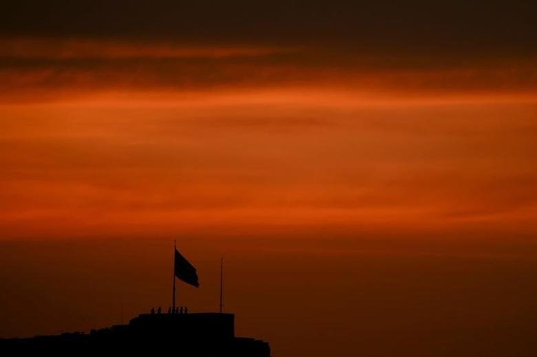 Greek soldiers are silhouetted during a ceremony to bring down the national flag atop the Acropolis hill during sunset in Athens, Greece, April 11, 2017. REUTERS/Alkis Konstantinidis - RTX355IT