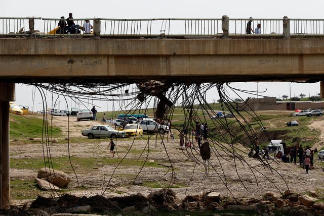 A ruined bridge is seen as Iraqi families and youths enjoy their Friday holiday at Shallalat district (Arabic for ''waterfalls'') in eastern Mosul, Iraq, April 21, 2017. REUTERS/ Muhammad Hamed