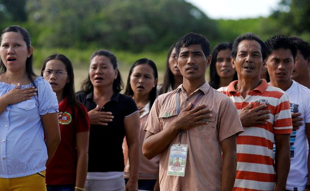 Filipinos living in Philippine occupied (Pagasa) Thitu island, in disputed South China Sea, sing the country's national anthem April 21, 2017.  REUTERS/Erik De Castro