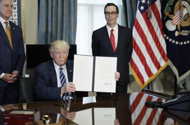 U.S. President Donald Trump (C) displays a financial services executive order as Treasury Secretary Steven Mnuchin (R) looks on during a signing ceremony at the Treasury Department in Washington, U.S., April 21, 2017. REUTERS/Kevin Lamarque