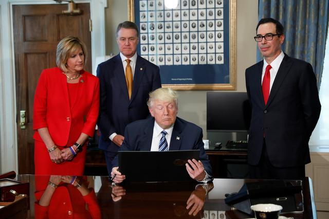U.S. President Donald Trump looks at an executive order accompanied by Congresswoman Claudia Tenney (R-NY), Sen. David Perdue (R-GA) and  Treasury Secretary Steve Mnuchin at the Treasury Department in Washington, U.S., April 21, 2017.  REUTERS/Aaron P. Bernstein