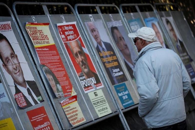 A man looks at campaign posters of the 11th candidates who run in the 2017 French presidential election in Enghien-les-Bains, near Paris, France April 19, 2017. REUTERS/Christian Hartmann/Files