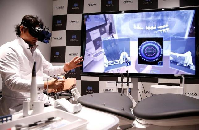 4月21日、ソフトバンクグループ傘下のリアライズ・モバイル・コミュニケーションズと歯科医療機器を手掛けるモリタは、複合現実(MR)技術を使った歯科治療シミュレーションシステムを報道陣に公開した。写真は都内で行われた同システムのデモンストレーションの様子(2017年 ロイター/Issei Kato)