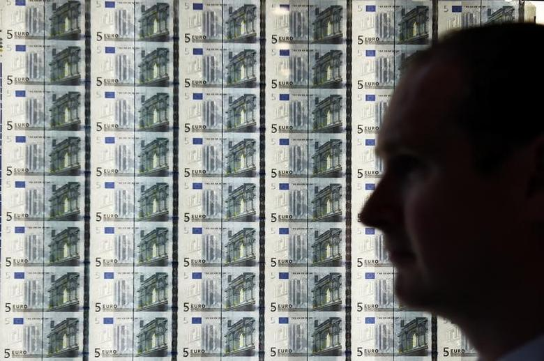 A man is seen in front of a sheet of five Euro notes at the opening of the new Central Bank of Ireland offices in Dublin, Ireland April 24, 2017. REUTERS/Clodagh Kilcoyne