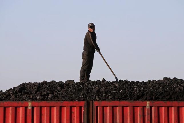 4月26日、中国国家発展改革委員会(発改委、NDRC)は、石炭産業の効率性向上を図るため、業界各社に合併やリストラを促し、一般炭が「妥当な」価格帯に戻るために措置を講じる方針を示した。写真はトラックに石炭を積み込む労働者。黒竜江省で2015年10月撮影(2017年 ロイター/Jason Lee)