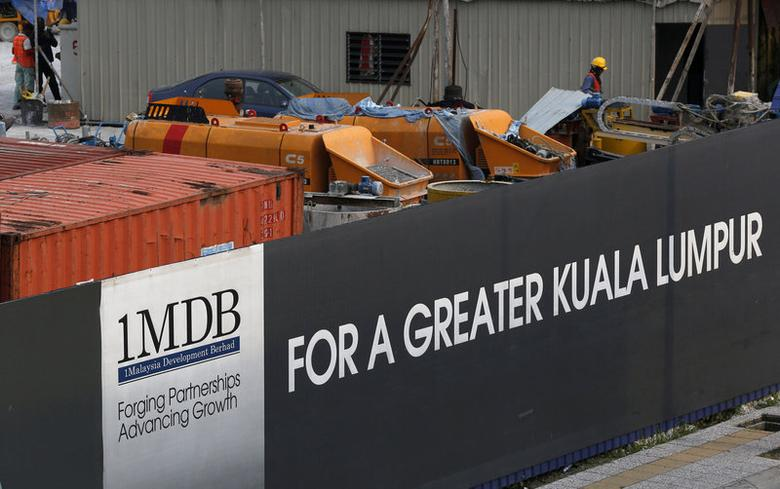 FILE PHOTO: Workmen are pictured on site at the 1 Malaysia Development Berhad (1MDB) flagship Tun Razak Exchange development in Kuala Lumpur, Malaysia, March 1, 2015.  REUTERS/Olivia Harris/File Photo