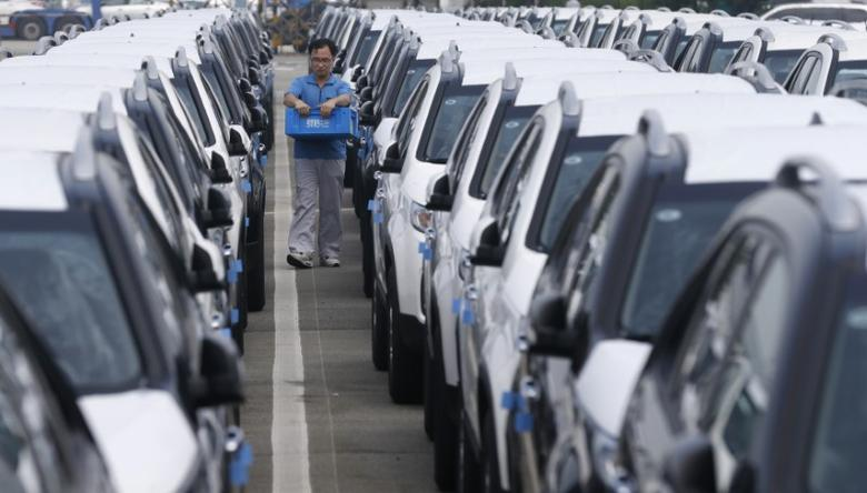 A worker checks cars made by South Korea's automakers Hyundai Motor and affiliate Kia Motors at their shipping yard at a port in Pyeongtaek, about 70 km (43 miles) south of Seoul July 25, 2013. REUTERS/Lee Jae-Won