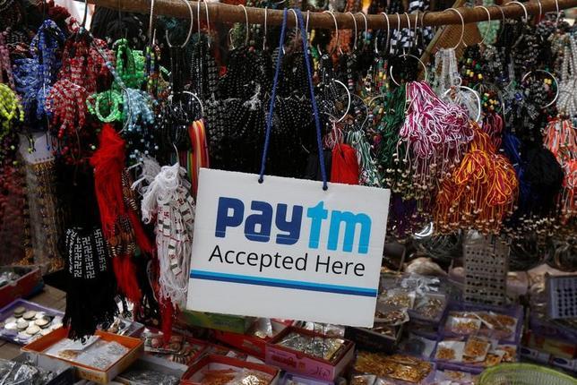 4月28日、インドの電子決済サービス「ペイティーエム」を運営するワン97コミュニケーションズは、ソフトバンクグループから1200億ルピー(18億7000万ドル)以上を調達する見通し。写真はインド・カルカッタの露店で、「ペイティーエム」使用可能のサイン。1月撮影(2017年 ロイター/Rupak De Chowdhuri)
