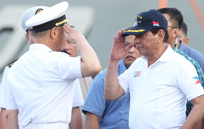 Philippine President Rodrigo Duterte returns the salute of a Chinese Navy officer as he tours a Chinese Naval ship during a visit to Davao city, southern Philippines May 1, 2017.  REUTERS/Lean Daval Jr/File Photo