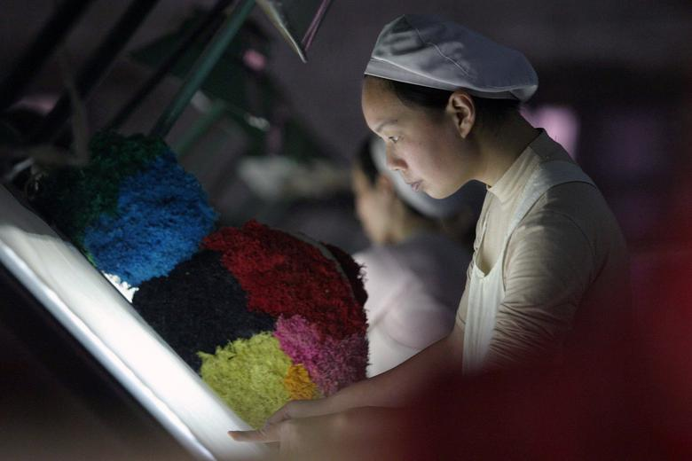 FILE PHOTO: A woman works at a textile factory in Xiangfan, Hubei province, China December 31, 2005.   REUTERS/Stringer/File Photo