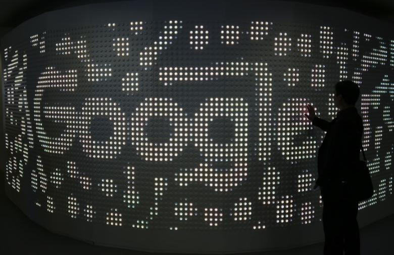 An attendee interacts with an illuminated panel at Google stand during the Mobile World Congress in Barcelona, Spain, March 1, 2017. REUTERS/Paul Hanna