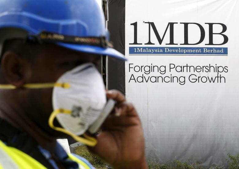 FILE PHOTO - A construction worker talks on the phone in front of a 1Malaysia Development Berhad (1MDB) billboard at the Tun Razak Exchange development in Kuala Lumpur, Malaysia, February 3, 2016. REUTERS/Olivia Harris/File Photo