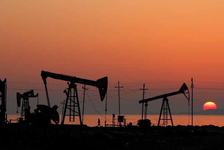 FILE PHOTO: Pump jacks are silhouetted against the rising sun on an oilfield in Baku, Azerbaijan, January 24, 2013.    REUTERS/David Mdzinarishvili/File Photo