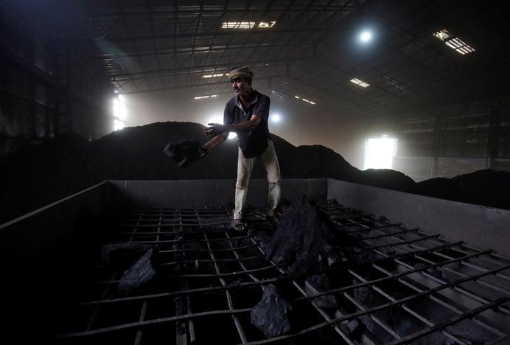A labourer works inside a coal yard on the outskirts of Ahmedabad, India, April 6, 2017. REUTERS/Amit Dave/Files