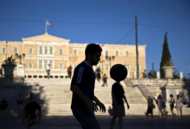 FILE PHOTO: A street performer plays with a ball at the Constitution (Syntagma) square near the Parliament building in Athens, Greece July 18, 2015. REUTERS/Ronen Zvulun /File Photo