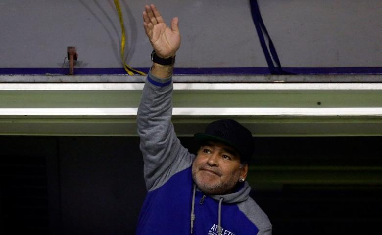 Former Argentine soccer star Diego Maradona waves as he attends the match.  REUTERS/Marcos Brindicci