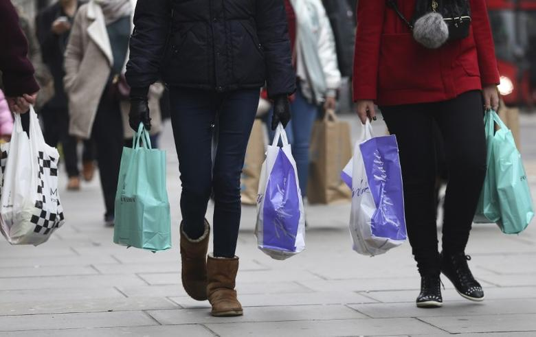 Shoppers carry bags on Oxford Street in London, Britain December 18, 2016. REUTERS/Neil Hall