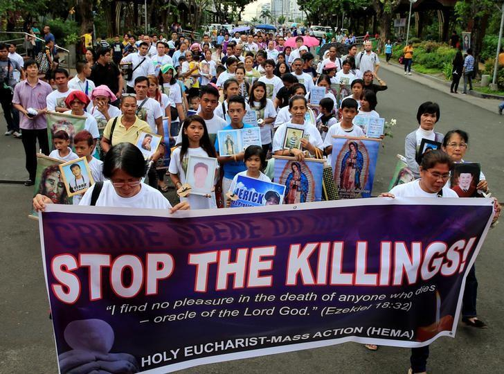 People hold photos of their family members, who they say were killed due to their alleged involvement in illegal drugs, during a protest against extra-judicial killings (EJK) while marching in an open area of a Roman Catholic Church in Paranaque city, metro Manila, Philippines March 2, 2017. REUTERS/Romeo Ranoco