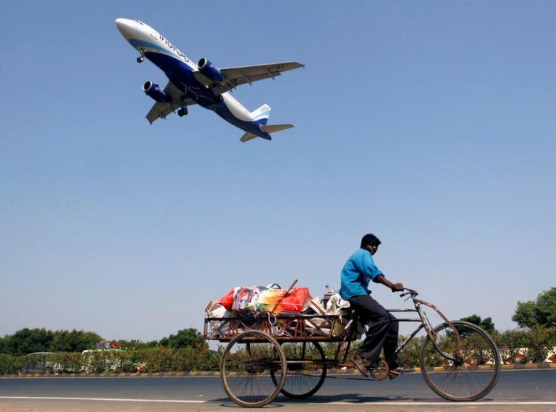 An IndiGo Airlines aircraft prepares to land as a man paddles his cycle rickshaw in Ahmedabad, October 26, 2015. REUTERS/Amit Dave/Files