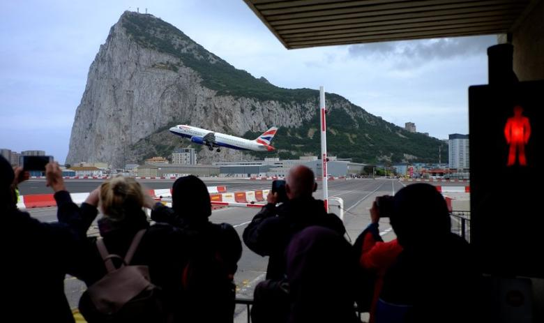 FILE PHOTO: Pedestrians take photographs of a British Airways plane as it flies past the Rock of Gibraltar as they wait to cross the airport runway in the British overseas territory of Gibraltar, historically claimed by Spain, April 20, 2017. REUTERS/Phil Noble
