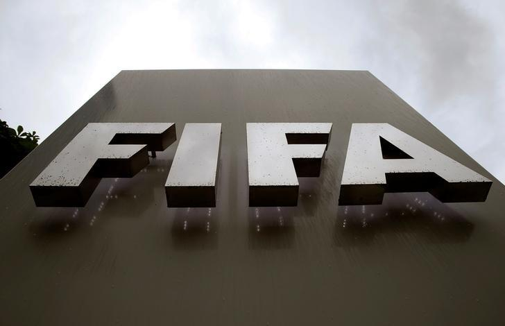 FILE PHOTO: Raindrops flow down on a logo in front of FIFA's headquarters in Zurich, Switzerland June 8, 2016. REUTERS/Arnd Wiegmann/Files