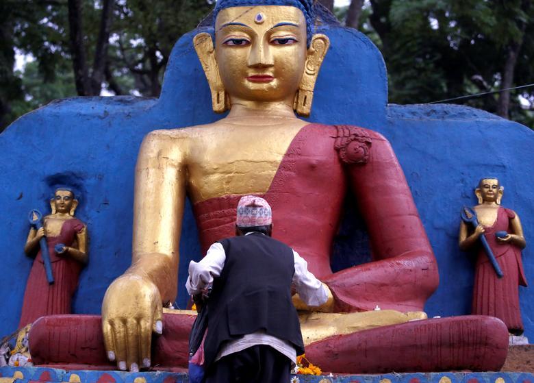 A devotee offers prayer on the idol of Buddha during the birth anniversary of Buddha, also known as Vesak Day, at Swayambhu in Kathmandu, Nepal. REUTERS/Navesh Chitrakar
