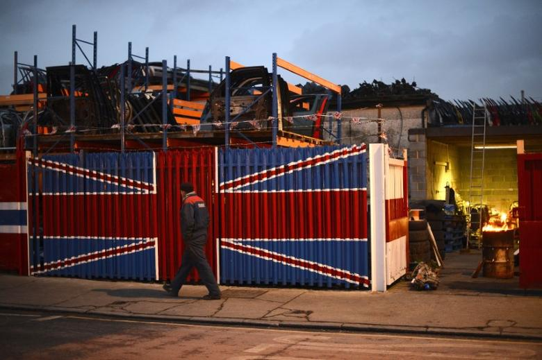 A man walks past a car scrap yard in east London January 25, 2013. REUTERS/Paul Hackett