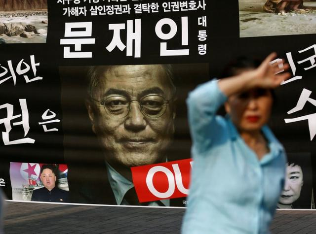 A woman walks past a placard opposing new South Korean President Moon Jae-in's policy on North Korea in Seoul, South Korea May 11, 2017. REUTERS/Kim Kyung-Hoon