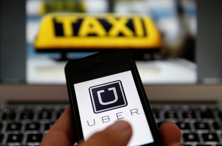 An illustration picture shows the logo of car-sharing service app Uber on a smartphone next to the picture of an official German taxi sign, September 15, 2014.    REUTERS/Kai Pfaffenbach/Illustration/File Photo