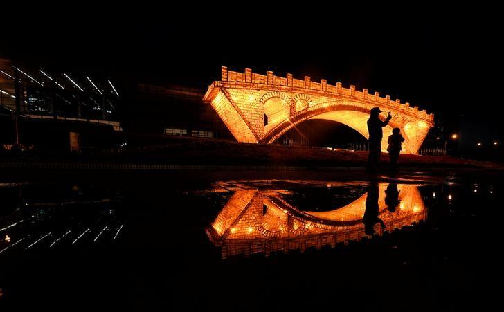 People take pictures in front of a ''Golden Bridge on Silk Road'' installation, set up ahead of the Belt and Road Forum, outside the National Convention Centre in Beijing, China May 11, 2017. Picture taken May 11, 2017. REUTERS/Stringer