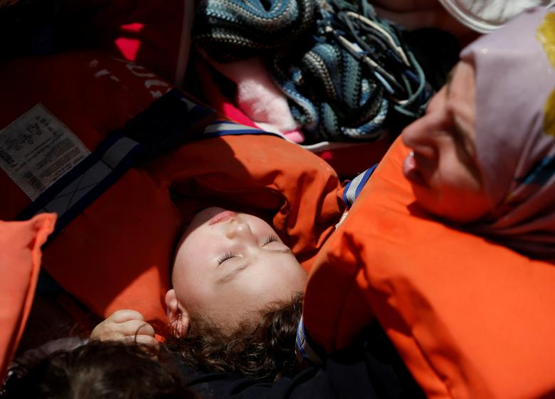File Photo: A child migrant lies in its mother's lap on a rigid-hulled-inflatable-boat (RHIB) alongside the Malta-based NGO Migrant Offshore Aid Station (MOAS) ship Phoenix during a rescue operation in the central Mediterranean, in international waters off the Libyan coastal town of Sabratha, May 4, 2017. REUTERS/Darrin Zammit Lupi/File Photo