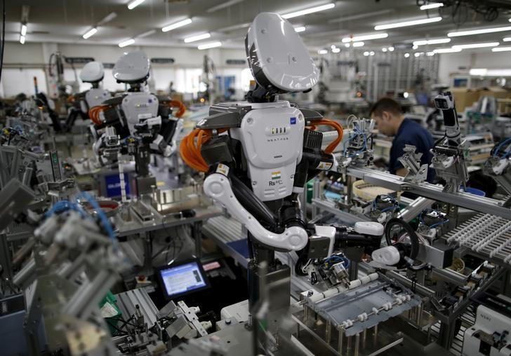 Humanoid robots work side by side with employees in the assembly line at a factory of Glory Ltd., a manufacturer of automatic change dispensers, in Kazo, north of Tokyo, Japan, July 1, 2015. REUTERS/Issei Kato/File Photo