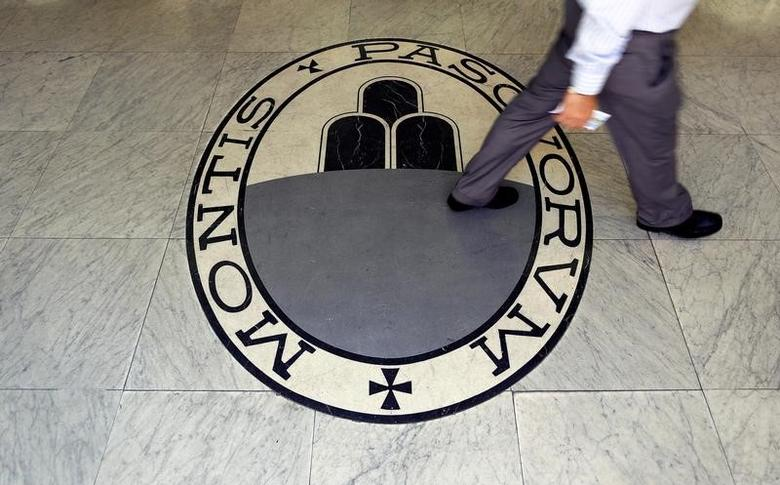 A man walks on a logo of the Monte Dei Paschi Di Siena bank in Rome, Italy September 24, 2013.  REUTERS/Alessandro Bianchi/Files