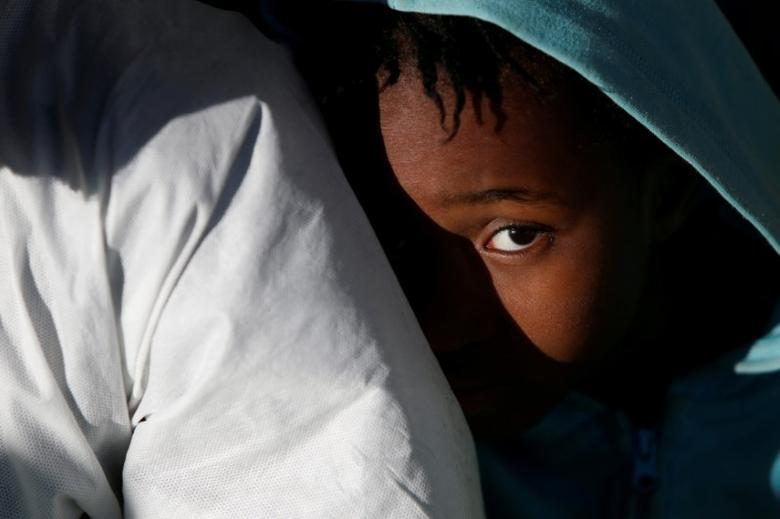 FILE PHOTO: A migrant child sits on the deck of the Malta-based NGO Migrant Offshore Aid Station (MOAS) ship Phoenix as it arrives with migrants and bodies on board, in Augusta, Italy April 19, 2017. REUTERS/Darrin Zammit Lupi/File Photo