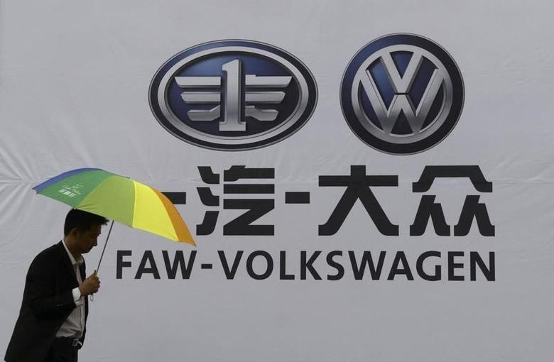 A man holds an umbrella as he walks past a company logo of FAW-Volkswagen at an automobile exhibition in Fuyang, China  REUTERS/Stringer