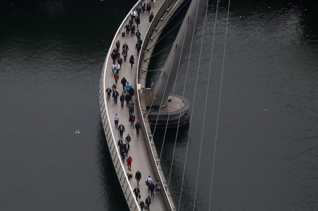 People cross a bridge in the Canary Wharf financial district in London, Britain May 17, 2017. REUTERS/Stefan Wermuth