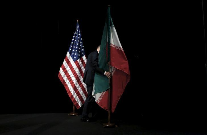 FILE PHOTO: A staff member removes the Iranian flag from the stage after a group picture with foreign ministers and representatives of the U.S., Iran, China, Russia, Britain, Germany, France and the European Union during the Iran nuclear talks at the Vienna International Center in Vienna, Austria July 14, 2015. REUTERS/Carlos Barria/File Photo