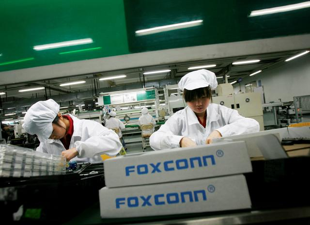 FILE PHOTO: Employees work inside a Foxconn factory in the township of Longhua in the southern Guangdong province May 26, 2010.      REUTERS/Bobby Yip/File Photo