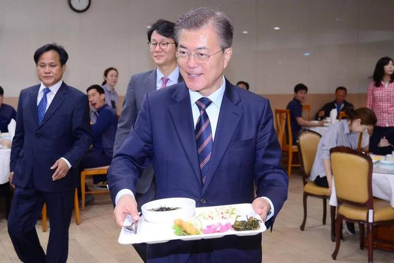 South Korean President Moon Jae-in carries a food tray as he has lunch with technical staff of the Presidential Blue House at an employee cafeteria of the Presidential Blue House in Seoul, South Korea May 12, 2017. Yonhap via REUTERS
