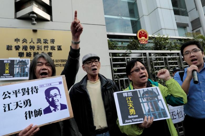 FILE PHOTO: Pro-democracy demonstrators hold up portraits of Chinese disbarred lawyer Jiang Tianyong, demanding his release, during a demonstration outside the Chinese liaison office in Hong Kong, China December 23, 2016. REUTERS/Tyrone Siu/File Photo