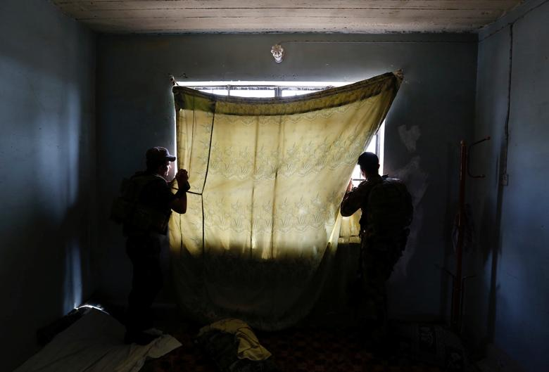 Members of Iraqi Counter Terrorism Service (CTS) forces look at the positions of Islamic State militants during clashes in western Mosul, Iraq, May 15, 2017. REUTERS/Danish Siddiqui