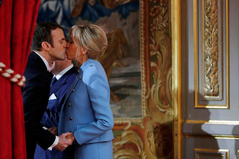 French President Emmanuel Macron kisses his wife Brigitte Trogneux during the handover ceremony in Paris, France, May 14, 2017. REUTERS/Philippe Wojazer
