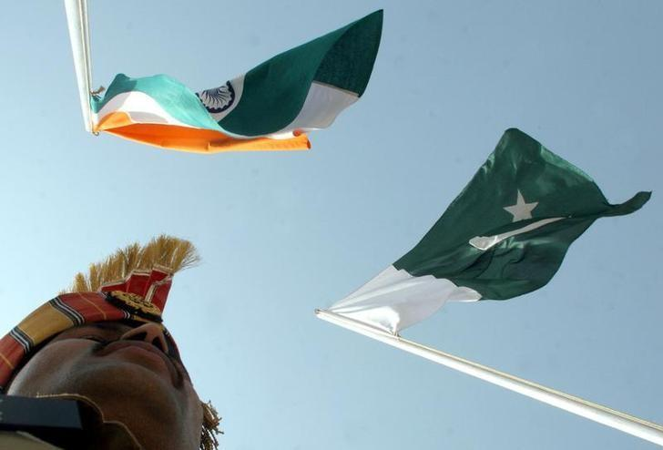 An Indian border guard stands near Indian (L) and Pakistani flags during a fair at Chamliyal in Jammu and Kashmir, June 22, 2006. REUTERS/Amit Gupta/Files