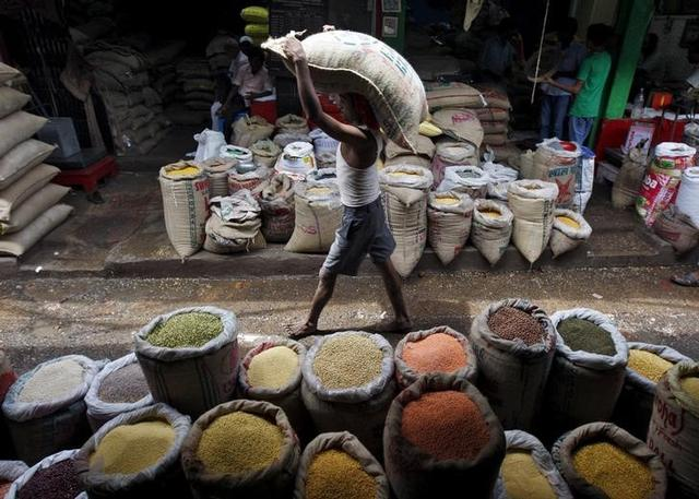 A labourer carries a sack filled with pulses at a wholesale pulses market in Kolkata, India, July 31, 2015. REUTERS/Rupak De Chowdhuri/Files