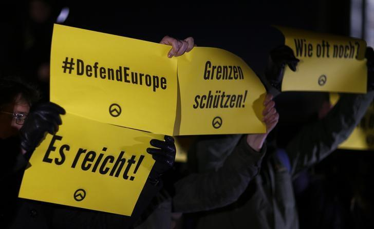 People hold placards with the logo of the far right Identitarian movement (Identitaere Bewegung) during a demonstration against German Chancellor Angela Merkel's migrant policy in front of the chancellery in Berlin, Germany, December 21, 2016, after a truck ploughed through a crowd at a Christmas market in the captial on Monday night. Placards read ''It's enough'', ''Protect borders'' and ''How many times again''.    REUTERS/Hannibal Hanschke