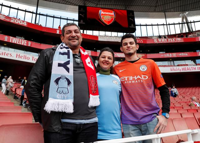 Matthaus Martins Fontes (R), a student from Ji-Parana in Brazil, poses for a photograph with his parents, Lucio (L) and Sandra, at a Premier League soccer match between Arsenal and Manchester City in London, Britain, April 2, 2017.  REUTERS/Eddie Keogh