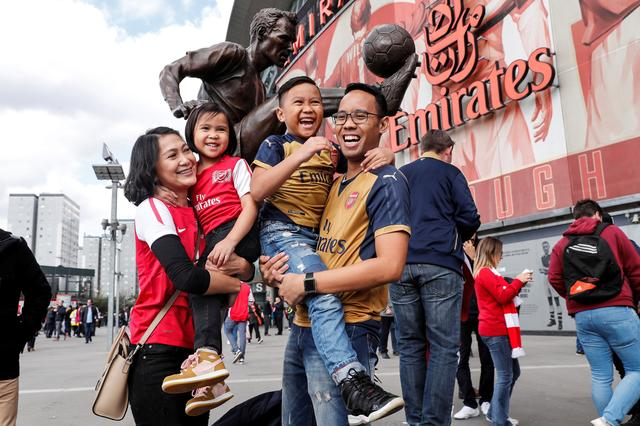 Audia Rizal Harahap from Jakarta in Indonesia, poses for a photograph with his wife and children, at a Premier League soccer match between Arsenal and Manchester City in London, Britain April 2, 2017.  REUTERS/Eddie Keogh